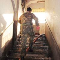 Uphill task: An army man climbing the stairs of the Nandaram market building, the upper floors of which are still caught in the raging inferno.