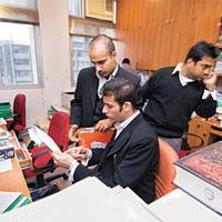 Getting their due: With Indian companies loosening their purse strings, young lawyers such as these at a law firm in New Delhi, are being tempted to stay back in the country and not seek greener pastu