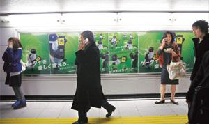 Plugged in: Even in the Tokyo subway, the Japanese cannot put down their cellphones.