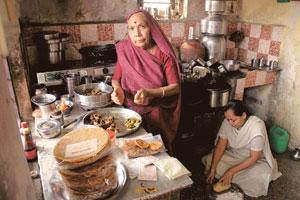 Local touch: Damayanti Thakkar (standing) makes snacks for Food Bazaar at her home in Mumbai's Dombivili suburb. She says she's got a new sense of self-respect when she see her own label in such a big