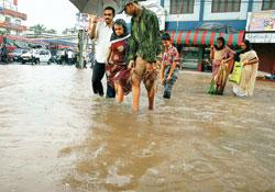 A file photo of people wading through an inundated road in Kochi, Kerala. It is uncertain if the unusually heavy rains in Kerala this month will affect the south-west monsoon