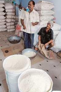 Taking stock: An Indian trader weighs rice in his shop at Miryalaguda Mandal in Nalgonda district of Andhra Pradesh. India, one of the biggest consumers of rice, is self-sufficient but has curbed its