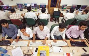 Holding tight: A file picture of trading at a stock brokerage firm in Mumbai. Markets in India are in a state of wait and watch as technology bellwether Infosys kicks off the earnings season this week