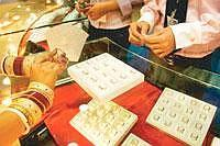 A file photograph of a woman checking out gold jewellery at a showroom on the outskirts of New Delhi