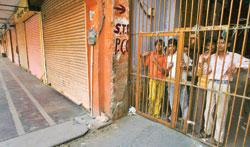 Children look on from behind a locked gate in the curfew-bound old city in Jaipur on Wednesday. Police imposed a day-long curfew to prevent any retaliatory violence (Photo by: Mustafa Quraishi / Mint)