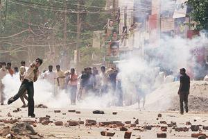 Pitched battle: Protesters pelt security personnel with stones and bricks during a demonstration at Aya Nagar in New Delhi on Thursday. Gujjars had called a bandh in the National Capital Region on Thu