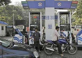 An attendant directs traffic at a Hindustan Petroleum gas station in Mumbai.  Bankers say Energy-related firms and companies poised to benefit from rising spending power in China and India will contin
