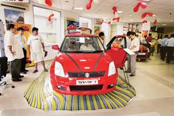 No small worry: Customers look at a Swift at a Maruti showroom in New Delhi. Environmentalists dread the impact of hundreds of thousands of smaller and cheaper cars hitting the?roads soon. (Photo: Blo