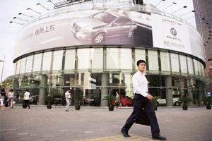 Growing big: Pedestrians walk past a Buick showroom in Shanghai. China's government realizes that its economy is in danger of overheating, but it has been reluctant to take severe measures to put the