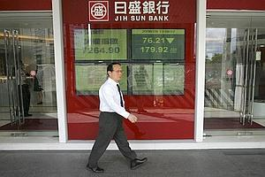 Bad show: A man walks past a monitor displaying stock prices in Taipei, Taiwan. Taiwanese shares fell nearly 4% on Tuesday.