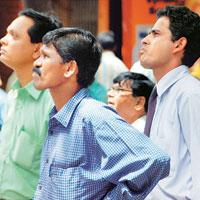 Multiple worries: Investors watching a screen of falling stock prices at the Bombay Stock Exchange on 8 July, when the Sensex slipped by 475 points. The Sensex closed at 13,469.85 on Friday, down 456