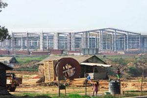 Ground rules: A file photo of the Tata Nano project at Singur. West Bengal is working on a policy whereby the purchasing firms will compensate land owners with alternative land and cash. (Subhankar Ch