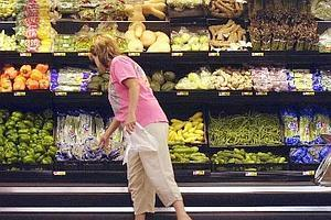 A shopper looks at produce at a Wal- Mart store in Rogers, Arkansas, US.  Wal-Mart says each of its reusable shopping bags eliminates the need for 100 plastic ones. It claims it has sold enough of the