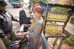 Costly supply: A women selling petrol in Karawang, Indonesia. Strong demand for the country's commodities has insulated it from slow growth but rising prices are beginning to hurt, particularly the po