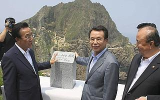 South Korean prime minister Han Seung-soo (C) and other officials celebrate after they installed a sign stone on the small cluster of islands, called Dokdo in Korean and Takeshima in Japanese. The lon
