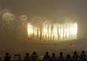 People watch fireworks illuminate the sky over the National Stadium during the opening ceremony of the Beijing 2008 Olympic Games on 8 August 2008. (Reuters photo)