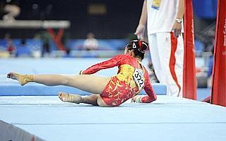 Chinese gymnast He Kexin falls down after performing at the uneven bars during the women's qualification rounds at the Beijing 2008 Olympics, 10 August. Photo: Julie Jacobson / AP