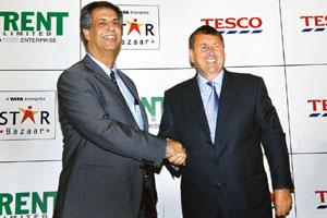 Step forward: Trent Ltd managing director Noel Tata (left) and Tesco international IT director Philip Clarke shake hands at a press conference in Mumbai on Tuesday to announce their cash-and-carry bus