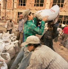Vital input: Workers carry cement bags at Noida. One of the biggest concerns facing the cement industry is the rising price of imported coal. Photograph: Harikrishna Katragadda / Mint