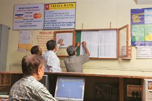 List of hopefuls: A file photo of Vijaya Bank officers in Mandya, Karnataka, putting up a list of farmers whose loans were waived. Photograph: Hemant Mishra / Mint