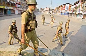 Keeping a watch: Security personnel patrol Lal Chowk in Srinagar during curfew on Sunday. Indefinite curfew was imposed in all 10 districts of Kashmir ahead of a protest march planned for Monday. Phot