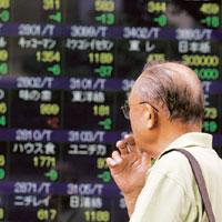 Lacklustre display: A man looks at a board displaying share prices in Tokyo. The Nikkei 225 index dropped 1.75% to 12,609.47 on Tuesday. Yuriko Nakao / Reuters