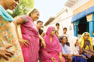 With baited breath: Women and children of Faridabad's Anangpur village gather on Tuesday, a day before the predicted end of the world, to discuss the European Organization for Nuclear Research's colli