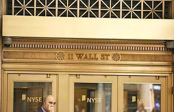A trader smokes a cigarette at an entrance to the New York Stock Exchange in the financial district of New York 19 September, 2008.  While most Americans have felt little effect from the turmoil on Wa