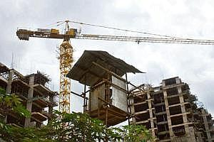 Short on funds: A file photo of a building complex under construction in Bangalore. RBI has made project commencement certificates from civic authorities mandatory for bank funding, adding to develope