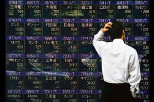 Property drag: A man looks at a video display showing Japanese stock prices in Tokyo on Tuesday. Property booms in Asia are turning to slowdowns, and threaten to slow the region's economy. Michael Car