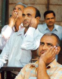 Unclear outlook: Investors react while watching the stock prices at a BSE screen on Thursday. The Sensex finally closed at around 10,581, down about 2.11%, thus recovering some 550 points. Shashank Pa