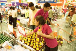 Cost-cutting: Employees (in pink T-shirts) at work in a Big Bazaar outlet at Noida. The retailer's parent Future Group has launched an internal cost-pruning campaign invoking staff pride in being stin