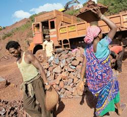Lagging behind: Labourers carry iron ore at a mine in Keonjhar, Orissa. The state has signed about 50  preliminary agreements to set up steel plants, but has not updated its mineral map for 30 years.