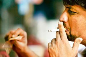 Puffing away: A file photo of a person smoking in Mumbai. A survey in New Delhi found that many of the 68 restaurants, bars, pubs and food courts were violating the smoking ban. Adeel Halim / Bloomber