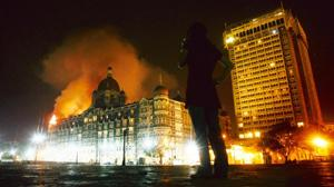 A reporter talks on her phone as smoke is seen coming from hotel Taj in Mumbai on Thursday. Arko Datta / Reuters