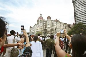 People take photographs of the damaged Taj Mahal hotel. Gurinder Osan / AP