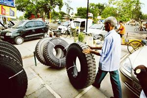 Troubled sector: A worker stacks Apollo truck tyres at an outlet in New Delhi. The financial slowdown has hit the automotive manfuacturing industry and companies such as Apollo are facing labour unres