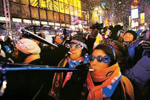 Hearty welcome: Revellers blow horns as the famous Waterford crystal ball drops at the New Year's eve festivities on Thursday in New York's Times Square. Bill and Hillary Clinton were present on the o