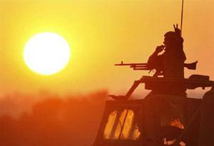 An Israeli soldier gestures atop a mobile artillery unit as the sun sets over the central Gaza Strip on 5 January 2009. Gil Cohen Magen / Reuters photo