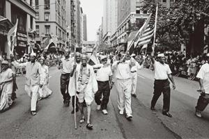 This photograph was taken by Ram Rahman in 2002, during an India Day parade in New York. A man dressed as Gandhi walks down Madison Avenue as others follow him, holding the tricolour in their hands. A