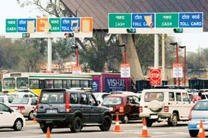 On track: Vehicles lined up at the toll plaza on the Delhi-Gurgaon highway. Currently, with most government-funded highways, private operators collect toll and sub-contractors are paid for maintenance