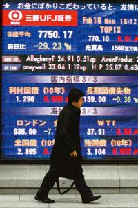 Dark days: A board shows share prices in Tokyo, Japan. Exporters were hurt as data showed the country's economy sank deeper into recession. Kim Kyung-Hoon / Reuters