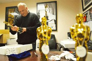 Recognizing excellence: Steve Miessner, the keeper of the Oscars, prepares the statuettes at Kodak Theatre in Los Angeles on Saturday. Many Hollywood personalities want the prize cycle to be shorter a