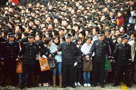 Sea of unemployed: A file photo of security workers restraining college students waiting to enter a job fair in Wuhan, in China's Hubei province. AP