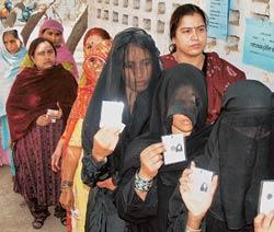 Electoral rights: Women show their identity cards at a polling booth in Bikaner. Nearly 60% turnout was registered for the state assembly polls.