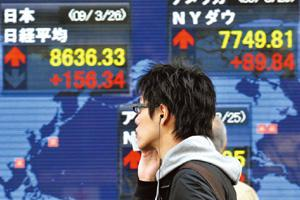Gains trimmed: A 26 March picture of a share prices board in Tokyo. On Friday, the market was initially strong, but closed in negative territory. Yoshikazu Tsuno / AFP