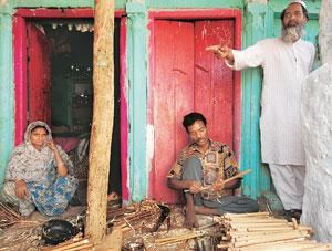 Fading music: Mohammad Usman (centre), makes flutes out of bamboo stalks as Mohammad Ilyas Siraj Ahmed (right), his relative, looks on. Pilibhit's flute makers can produce a litany of reasons that led