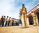 Securing the vote: People line up to cast their votes as security personnel stand guard at a polling booth in Madangundi village, near Ranchi. Reuters