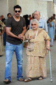 Bollywood actor John Abraham lends a helping hand to an elderly woman as she leaves after casting her vote at a polling booth in Mumbai on Thursday. AFP Photo