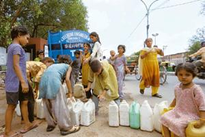 Hefty bills: Slum children queue up to fill water from a Delhi Jal Board tanker. Most households in New Delhi's Sangam Vihar spend Rs300-500 a month for buying water from private suppliers. Ramesh Pat